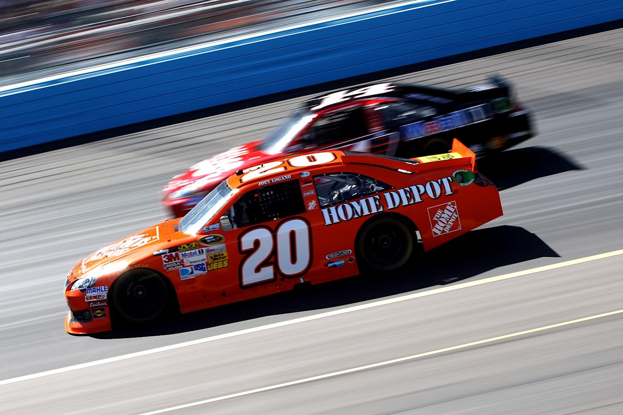 AVONDALE, AZ - MARCH 04:  Joey Logano, driver of the #20 The Home Depot Toyota, drives alongside Tony Stewart, driver of the #14 Office Depot/ Mobil 1 Chevrolet, during the NASCAR Sprint Cup Series SUBWAY Fresh Fit 500 at Phoenix International Raceway on March 4, 2012 in Avondale, Arizona.  (Photo by Christian Petersen/Getty Images)