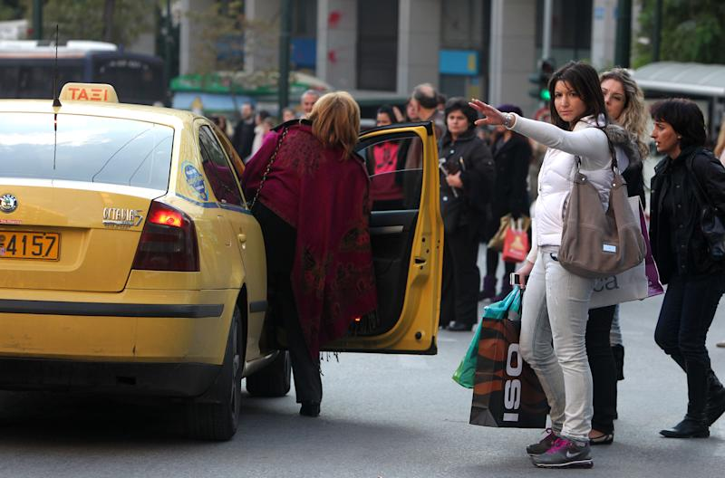 People flag down taxis during a public transport strike in Athens on Monday, Dec. 13, 2010. Workers at public transport services and a state-owned bank began strikes Monday, starting off a week of protests against a shake-up of labor rules in crisis-hit Greece. Transport services in greater Athens halted for more than six hours, a day before parliament was due to vote on the proposed changes that include deeper pay cuts for employees at state companies and a reduction of collective bargaining rights in the private sector. (AP Photo/Petros Giannakouris)