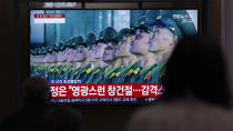 """People wearing face masks watch a TV screen during a news program reporting about the ceremony to mark the 75th founding anniversary of the North Korea's ruling Workers' party, at the Seoul Railway Station in Seoul, South Korea, Saturday, Oct. 10, 2020. A part of letters read on the top """"A military parade to mark the 75th founding anniversary of the North Korea's ruling Workers' party."""" (AP Photo/Lee Jin-man)"""