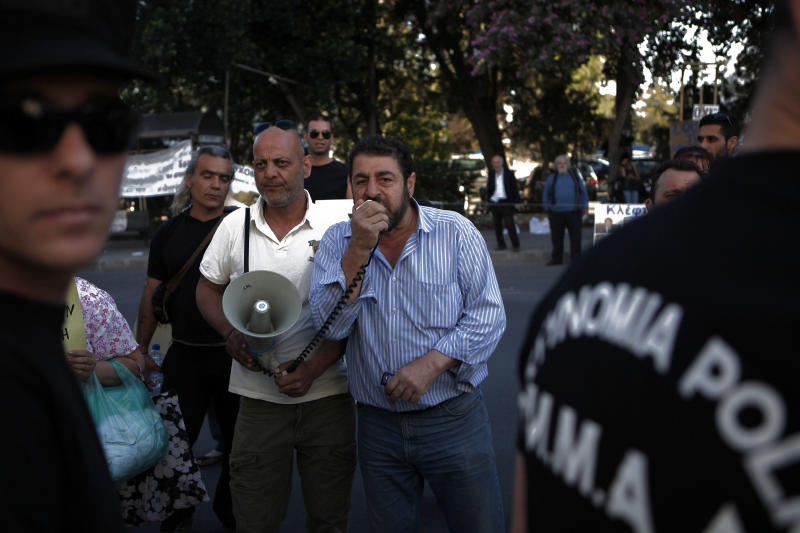 Protesters shout slogans behind riots police, during an anti-bailout protest outside of the Cyprus' parliament,  in capital Nicosia, Thursday, April 25, 2013. Cyprus' central bank says the Romanian operations of the island nation's largest lender Bank of Cyprus will resume April 26th after being suspended for more than three weeks amid plans to sell them off. (AP Photo/Petros Karadjias)