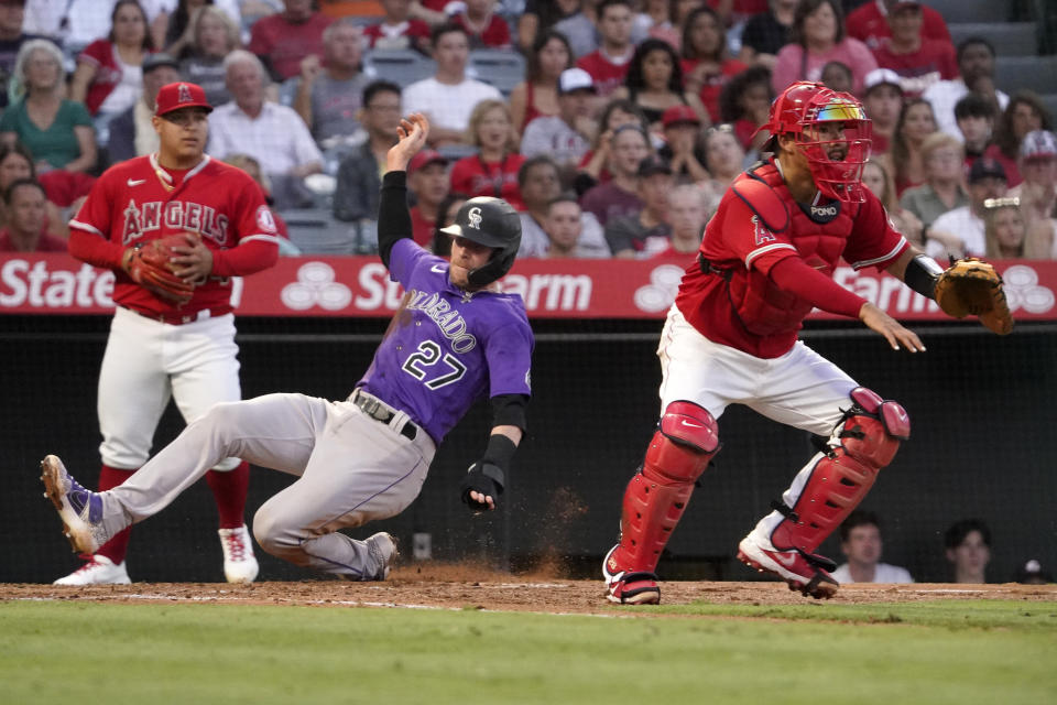 Colorado Rockies' Trevor Story, center, scores on a single by Ryan McMahon as Los Angeles Angels catcher Kurt Suzuki, right, waits for the ball as starting pitcher Jose Suarez backs him up during the third inning of a baseball game Tuesday, July 27, 2021, in Anaheim, Calif. (AP Photo/Mark J. Terrill)