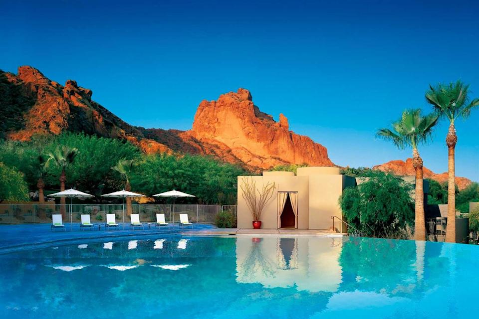 Infinity pool under palm trees and red rocks at Sanctuary on Camelback Mountain Resort & Spa in Scottsdale, Arizona