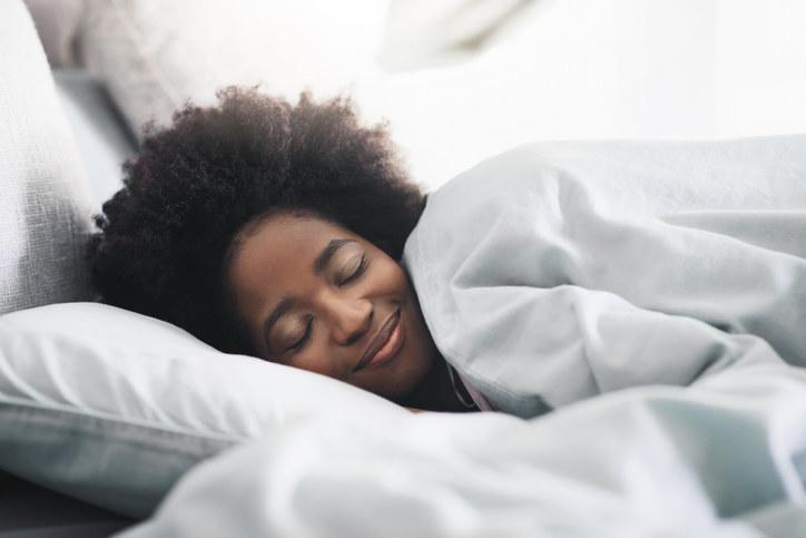 A person smiling as they lie in bed