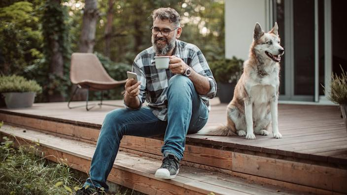 Mature men at his cottage resting on pprch with his dog.