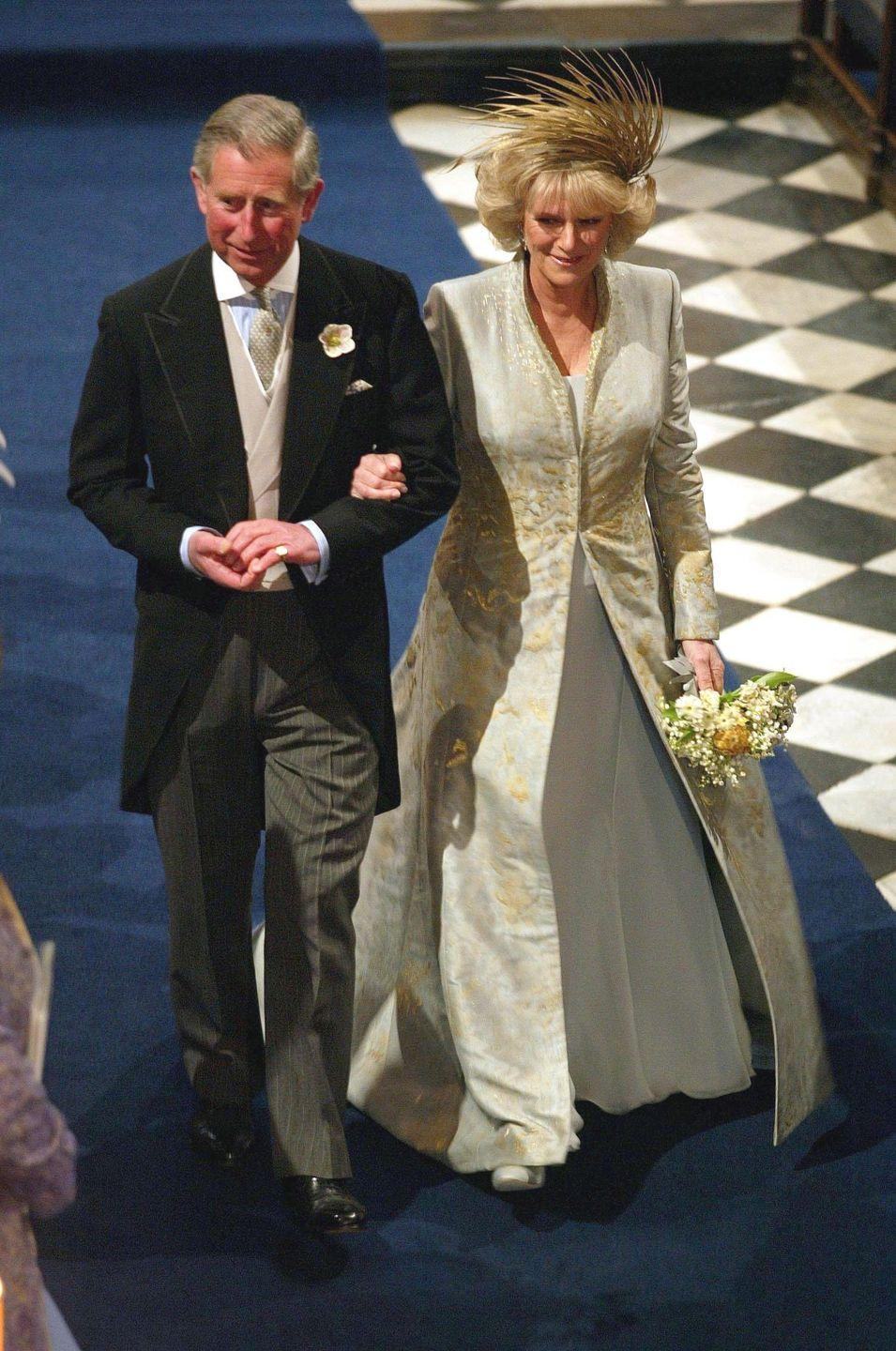 """<p>For her second marriage to Prince Charles, Camilla chose a look from <a href=""""https://www.popsugar.com/fashion/photo-gallery/44447684/image/44447696/Camilla-Parker-Bowles-2005"""" rel=""""nofollow noopener"""" target=""""_blank"""" data-ylk=""""slk:Robinson Valentine"""" class=""""link rapid-noclick-resp"""">Robinson Valentine</a> (now known as Anna Valentine) that included a white gown with a gold embroidered coat. She accessorized with a standout gold headpiece. </p>"""