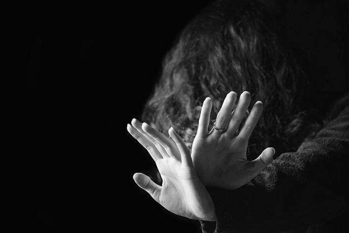 Concept of a violence against women. Black and white portrait of scared and desperate woman, focus on the hands in protective gesture