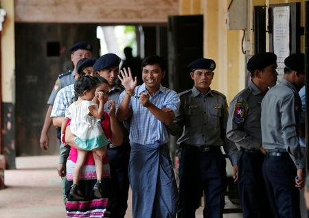 Detained Reuters journalist Wa Lone (C) escorted by police and his wife arrives for a court hearing in Yangon