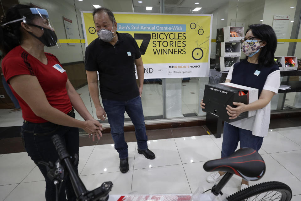 Benjamin Canlas Courage to be Kind Foundation founder Dr. George Canlas, center, and his wife co-founder Dr. Glennda Canlas, right, talk to a recipient before they handover a bicycle and safety equipment at the financial district of Manila, Philippines, Saturday, July 11, 2020. Restricted public transportation during the lockdown left many Filipinos walking for hours just to reach their jobs. The foundation saw the need and gave away mountain bikes to nominated individuals who are struggling to hold on to their jobs in a country hard hit by the coronavirus. (AP Photo/Aaron Favila)