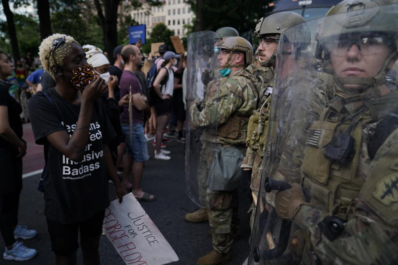 Soldiers with Utah National Guard stand near a group of demonstrators that gathered to protest the death of George Floyd, Wednesday, June 3, 2020, near the White House in Washington. Floyd died after being restrained by Minneapolis police officers. (AP Photo/Evan Vucci)