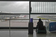 A passenger sits on her luggage watching passenger airplanes parked on the tarmac after all flights were canceled at Pudong International Airport in Shanghai, China, Sunday, July 25, 2021. Airline flights were canceled in eastern China and cargo ships were ordered out of the area Saturday as Typhoon In-fa churned toward the mainland after dumping rain on Taiwan. (AP Photo/Andy Wong)
