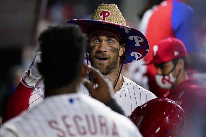 Philadelphia Phillies' Bryce Harper, center, and Jean Segura celebrate in the dugout after Harper's home run against Colorado Rockies pitcher Tyler Kinley during the seventh inning of a baseball game, Saturday, Sept. 11, 2021, in Philadelphia. (AP Photo/Matt Slocum)