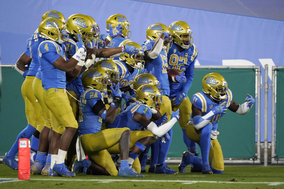UCLA players pose for photos after intercepting an Arizona pass during the second half of an NCAA college football game Saturday, Nov. 28, 2020, in Pasadena, Calif. (AP Photo/Marcio Jose Sanchez)