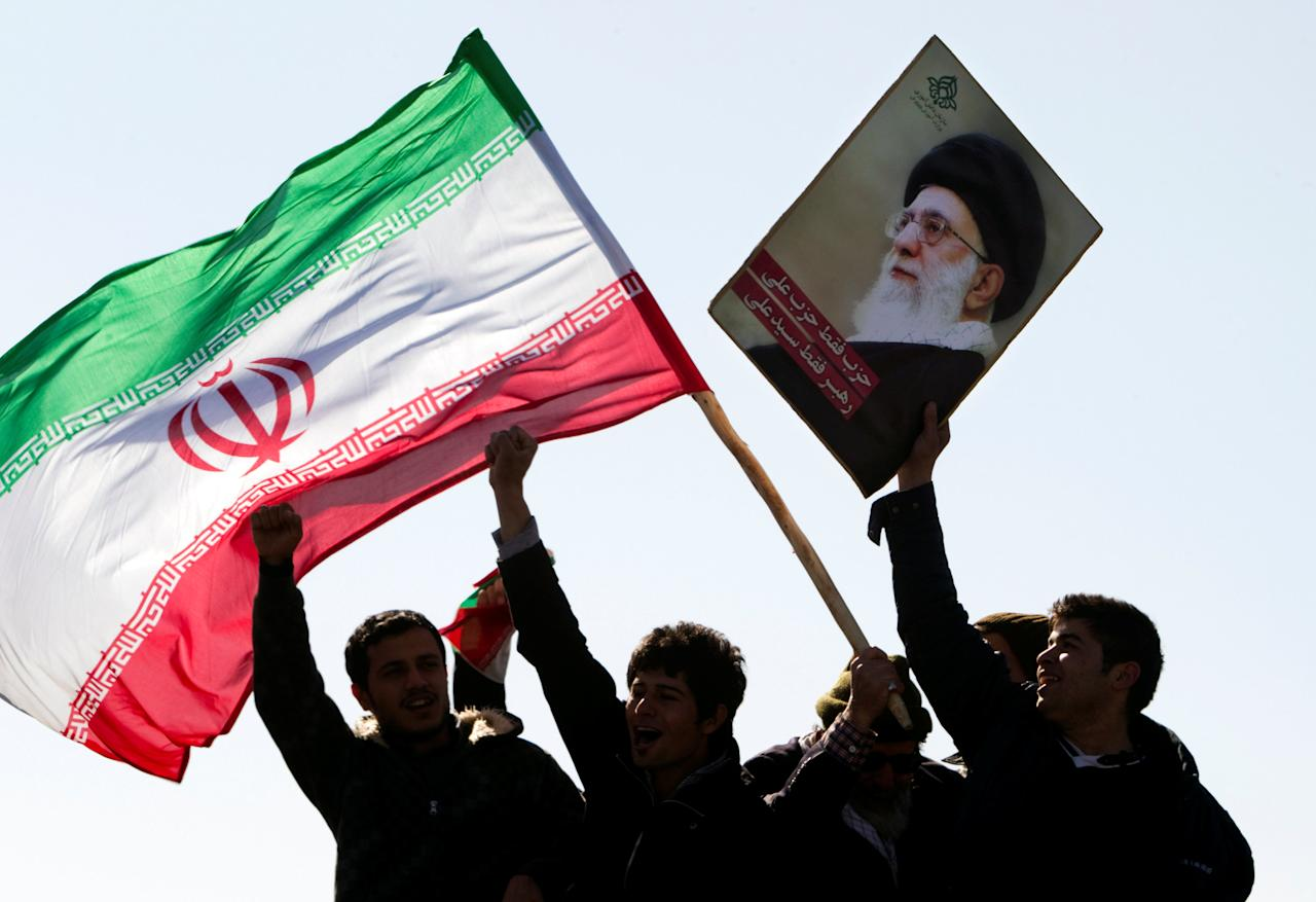 FILE PHOTO: Demonstrators wave Iran's flag and hold up a picture of supreme leader Ayatollah Ali Khamenei during a ceremony to mark the 33rd anniversary of the Islamic Revolution, in Tehran's Azadi square February 11, 2012.    To match Special Report MIDEAST-CRISIS/IRAQ-NUJABA   REUTERS/Raheb Homavandi/File Photo