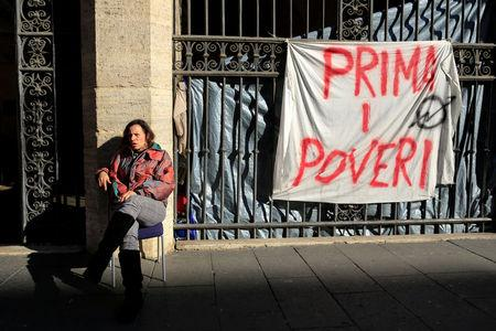 """Angela Grossi sits next to a banner reading """"Poor first"""", hanging in a gate of the portico of the Basilica of the Santi Apostoli in Rome"""
