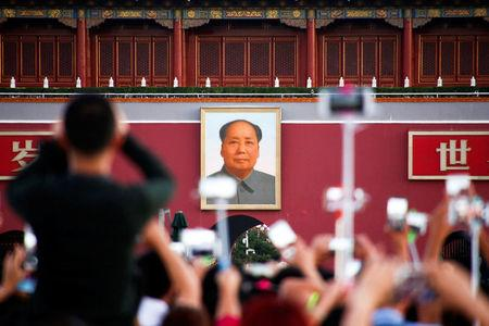 People take pictures during the flag raising ceremony on Tiananmen Square