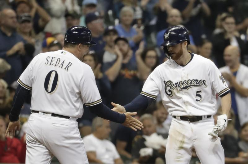 Milwaukee Brewers' Cory Spangenberg is congratulated by third base coach Ed Sedar after hitting a two-run scoring triple during the fourth inning of a baseball game against the San Diego Padres Monday, Sept. 16, 2019, in Milwaukee. (AP Photo/Morry Gash)