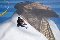 FILE - In this April 17, 2019 file photo, mural artist Gustavo Zermeno Jr. poses for photos on a basketball court mural he dedicated to slain rapper Nipsey Hussle in Los Angeles. Hussle, 33, was shot and killed outside his Los Angeles clothing store on March 31, 2019. A year after Hussle's death, his popularity and influence are as strong as ever. He won two posthumous Grammys in January, he remains a favorite of his hip-hop peers and his death has reshaped his hometown of Los Angeles in some unexpected ways. (AP Photo/Jae C. Hong, File)