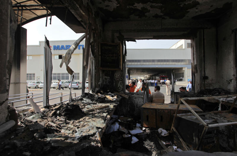 A reception block of Maruti Suzuki factory is burnt down in Manesar, near New Delhi, India, Thursday, July 19, 2012. According to news reports, one person died and at least 40 people were injured in Wednesday's labor unrest at the Manesar facility of India's largest passenger car maker. (AP Photo/ Saurabh Das)