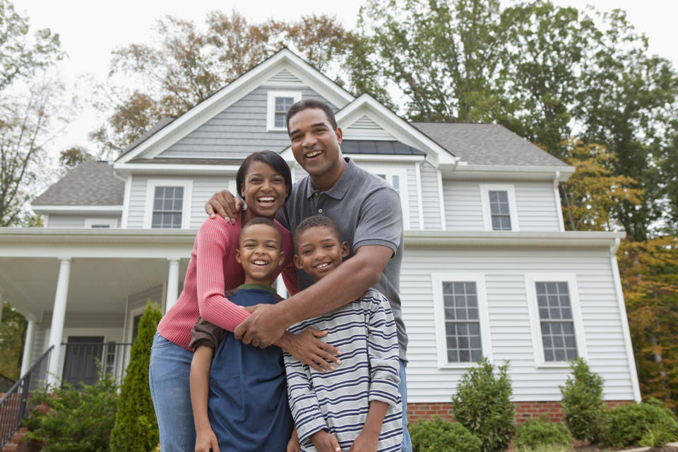 Black family standing together in front of house