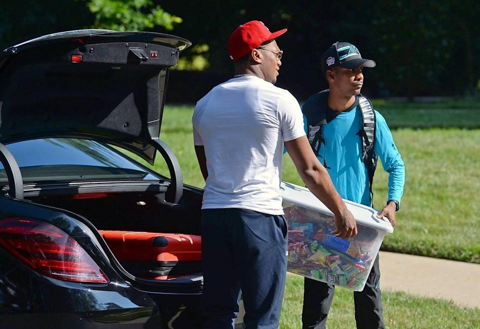 Carolina Panthers wide receiver DJ Moore gets an assist unloading a tub of candy and snacks from his trunk at the team's dormitory at Wofford College Tuesday.