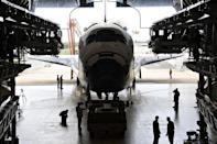 The space shuttle Atlantis is towed into its hangar at the Orbiter Processing Facility at Kennedy Space Center in Florida. The shuttle Atlantis cruised home for a final time Thursday, ending its last mission to the International Space Station and closing a 30-year chapter in American space exploration