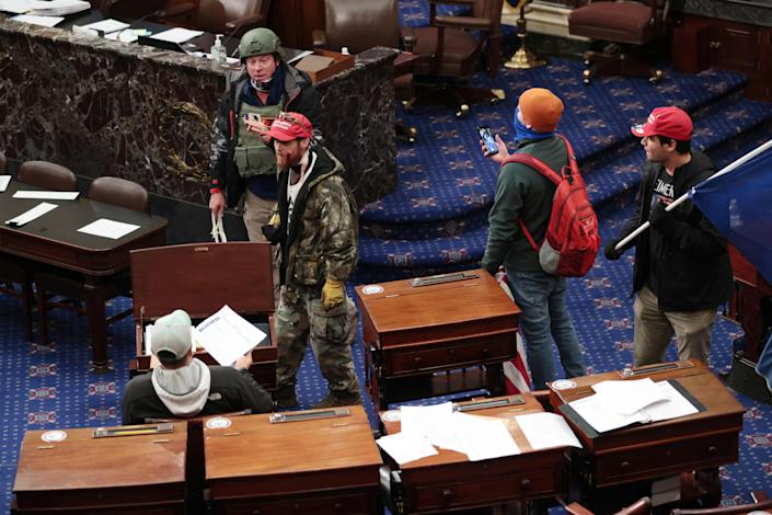 Protesters enter the Senate Chamber on January 6, 2021, in Washington, D.C. Brock is allegedly seen in this photo wearing a green helmet and camo jacket. / Credit: Getty Images