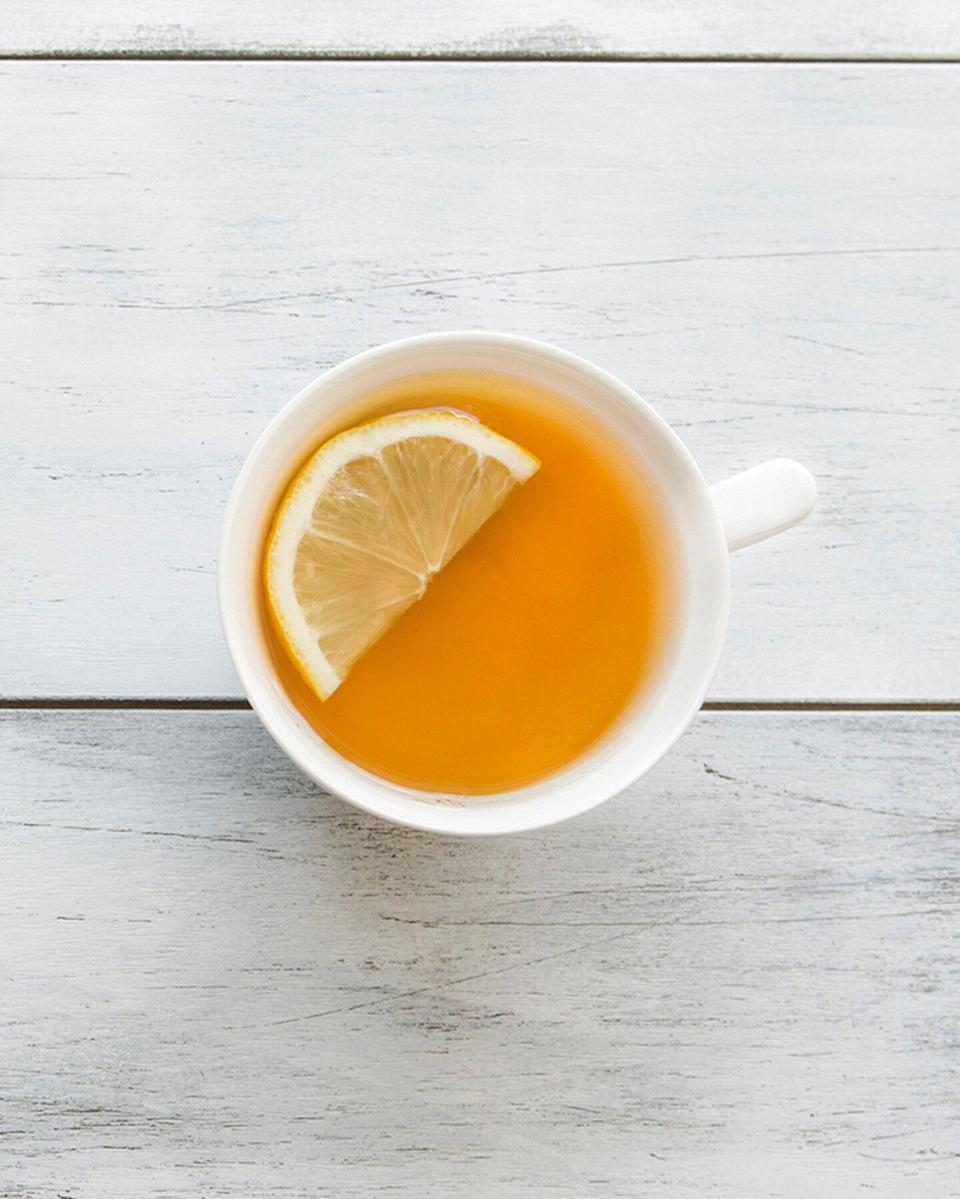 cup of ginger tea with a wedge of lemon