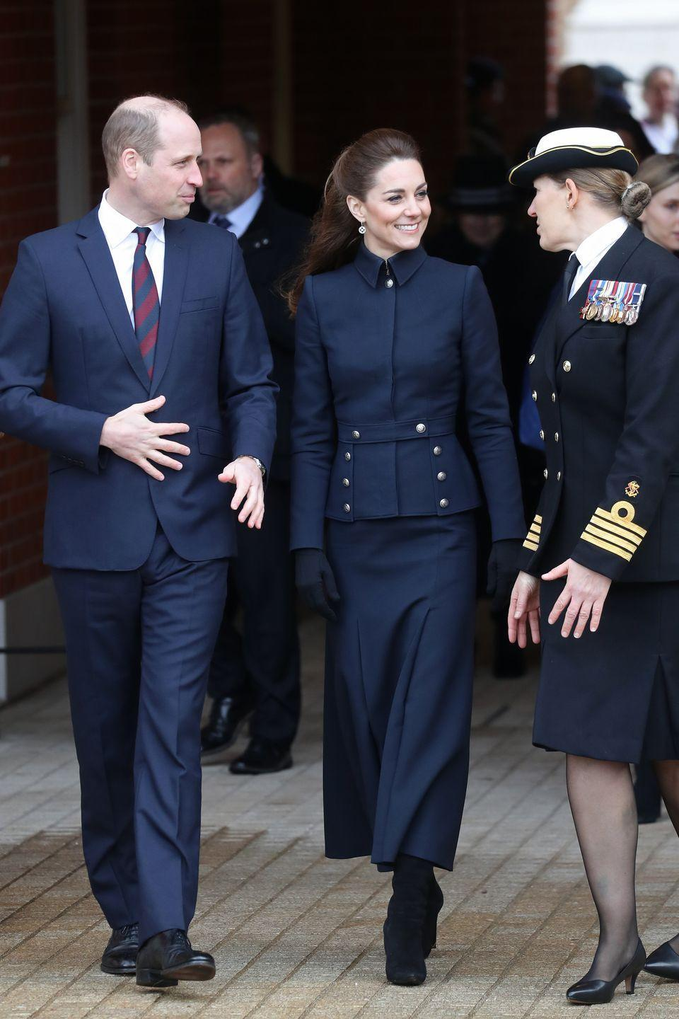 """<p>Kate and Prince William accompanied Prince Charles and Camilla on <a href=""""https://www.townandcountrymag.com/society/tradition/a30859150/kate-middleton-prince-william-charles-camilla-rare-appearance-military-rehab-leicester/"""" rel=""""nofollow noopener"""" target=""""_blank"""" data-ylk=""""slk:a visit to Leicestershire"""" class=""""link rapid-noclick-resp"""">a visit to Leicestershire</a>, where they toured a rehabilitation center for members of the armed forces. The Duchess chose a military-inspired, navy blue <a href=""""https://www.townandcountrymag.com/society/tradition/a30859254/kate-middleton-mcqueen-military-coat-leicestershire-photos/"""" rel=""""nofollow noopener"""" target=""""_blank"""" data-ylk=""""slk:Alexander McQueen jacket and skirt"""" class=""""link rapid-noclick-resp"""">Alexander McQueen jacket and skirt</a> for the occasion. She completed the look with black heeled boots, black gloves, and drop earrings. </p>"""