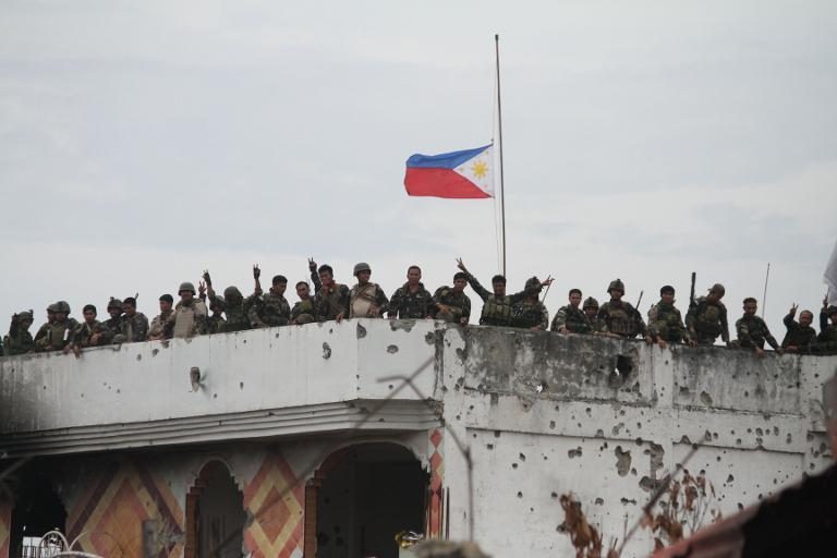 Philippine soldiers celebrate on the roof of a damaged house following heavy fighting against Islamist militants in Zamboanga on September 28, 2013