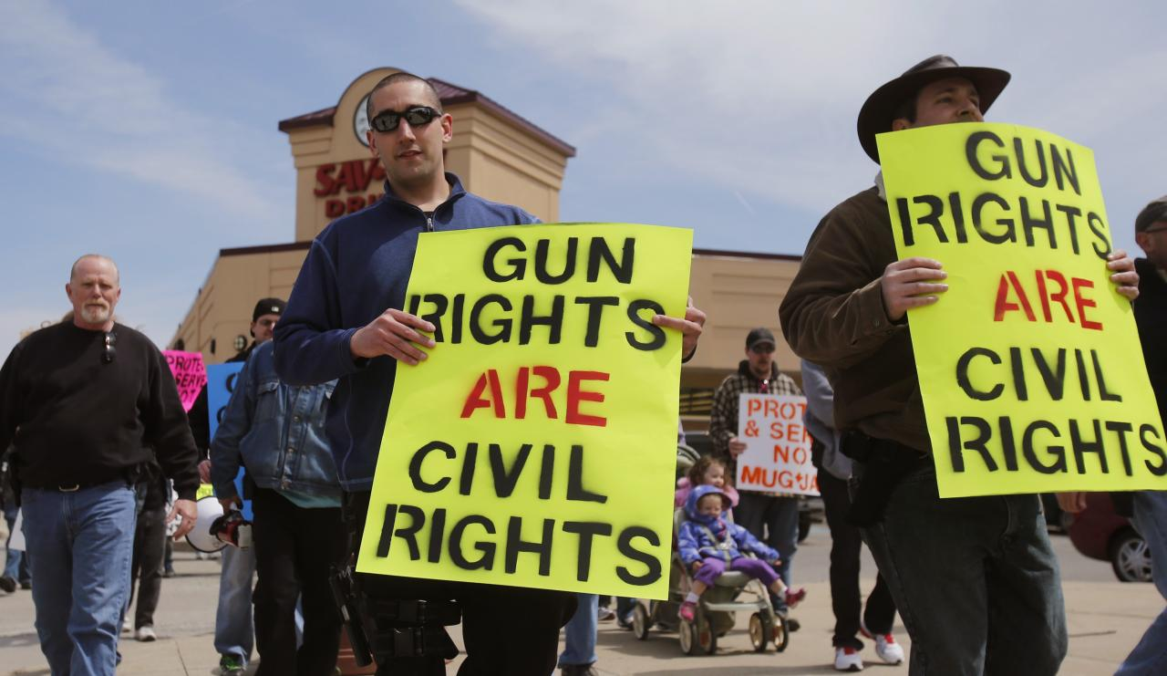 Open Carry gun supporters carry signs and guns strapped to their hips during a rally in support of the Michigan Open Carry gun law in Romulus, Michigan April 27, 2014. REUTERS/Rebecca Cook (UNITED STATES - Tags: CIVIL UNREST POLITICS SOCIETY)