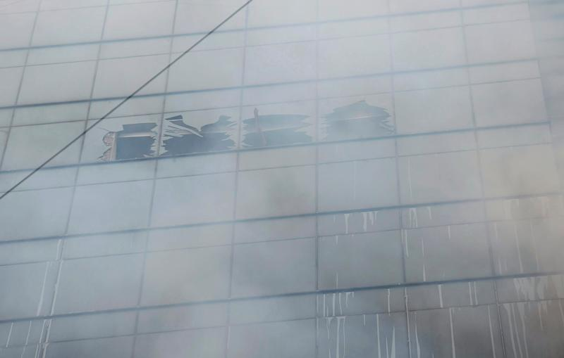 A hand sticks out of a broken glass in a multi-storied office building that caught fire in Dhaka, Bangladesh, March 28, 2019. (AP Photo/Mahmud Hossain Opu )