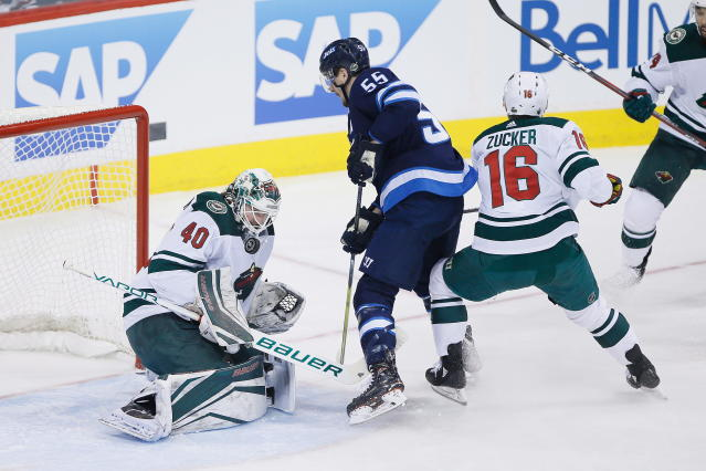 Minnesota Wild goaltender Devan Dubnyk (40) saves the shot from Winnipeg Jets' Mark Scheifele (55) as Jason Zucker (16) defends during the first period in Game 5 of an NHL hockey first-round playoff series in Winnipeg, Manitoba, Friday, April 20, 2018. (John Woods/The Canadian Press via AP)