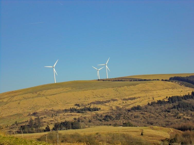 Wind turbines on a green hillside.