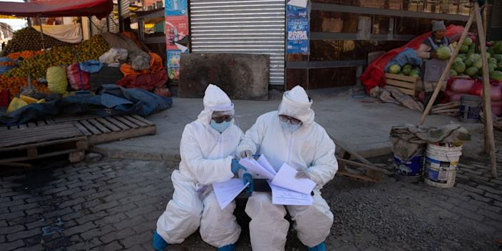 """Healthcare workers dressed in full protective gear organize their documents of data they have collected during a house-to-house new coronavirus testing drive, ringed by a produce market in the Villa Dolores neighborhood of El Alto, Bolivia, Saturday, July 18, 2020. <p class=""""copyright""""><a href=""""http://www.apimages.com/metadata/Index/APTOPIX-Virus-Outbreak-Bolivia/9a084de3837145efa5da15d1cf1244d4/1/0"""" rel=""""nofollow noopener"""" target=""""_blank"""" data-ylk=""""slk:Juan Karita/AP"""" class=""""link rapid-noclick-resp"""">Juan Karita/AP</a></p>"""