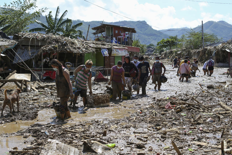 Residents walk through mud and debris as they return to retrieve belongings from the typhoon-damaged Kasiglahan village in Rodriguez, Rizal province, Philippines on Friday, Nov. 13, 2020. Thick mud and debris coated many villages around the Philippine capital Friday after Typhoon Vamco caused extensive flooding that sent residents fleeing to their roofs and killing dozens of people. (AP Photo/Aaron Favila)