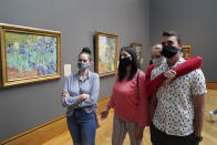 """FILE - In this Wednesday, May 26, 2021 file photo, visitors wear masks as they view art, including Vincent van Gogh's """"Irises"""", at left, at the newly re-opened Getty Center amid the COVID-19 pandemic in Los Angeles. Los Angeles County residents are again required to wear masks indoors regardless of their vaccination status, a new mandate starting this weekend that health officials hope will reverse the latest spikes in coronavirus cases, hospitalizations and deaths. The rule went into effect late Saturday, July 17, for the nation's largest county, home to 11 million people, where a sharp increase in COVID-19 cases is led by the highly transmissible delta variant. (AP Photo/Marcio Jose Sanchez, File)"""