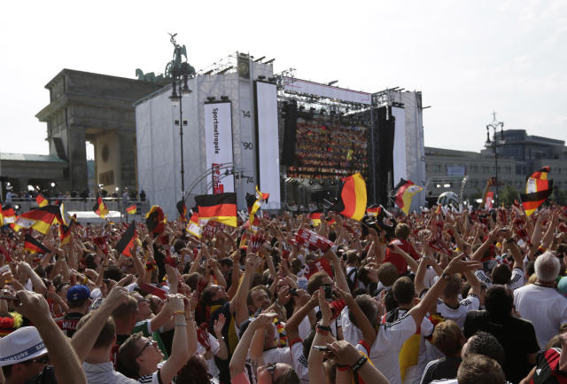 Fans take pictures of the plane with the German team on board that flies over the stage at the Brandenburg gate prior to the arrival of the German national soccer team in Berlin Tuesday, July 15, 2014. Germany beat Argentina 1-0 on Sunday to win its fourth World Cup title. (AP Photo/Petr David Josek)