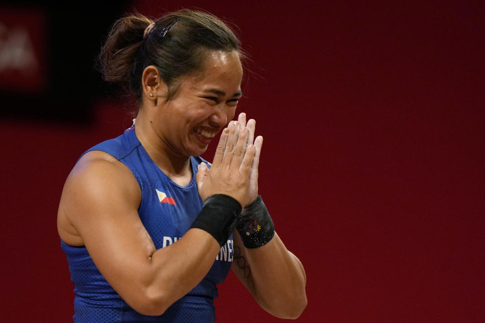 CORRECTS TO HIDILYN DIAZ OF PHILIPPINES FROM ANA GABRIELA LOPEZ FERRER OF MEXICO - Hidilyn Diaz of Philippines celebrates after a lift as she competes in the women's 55kg weightlifting event, at the 2020 Summer Olympics, Monday, July 26, 2021, in Tokyo, Japan. (AP Photo/Luca Bruno)
