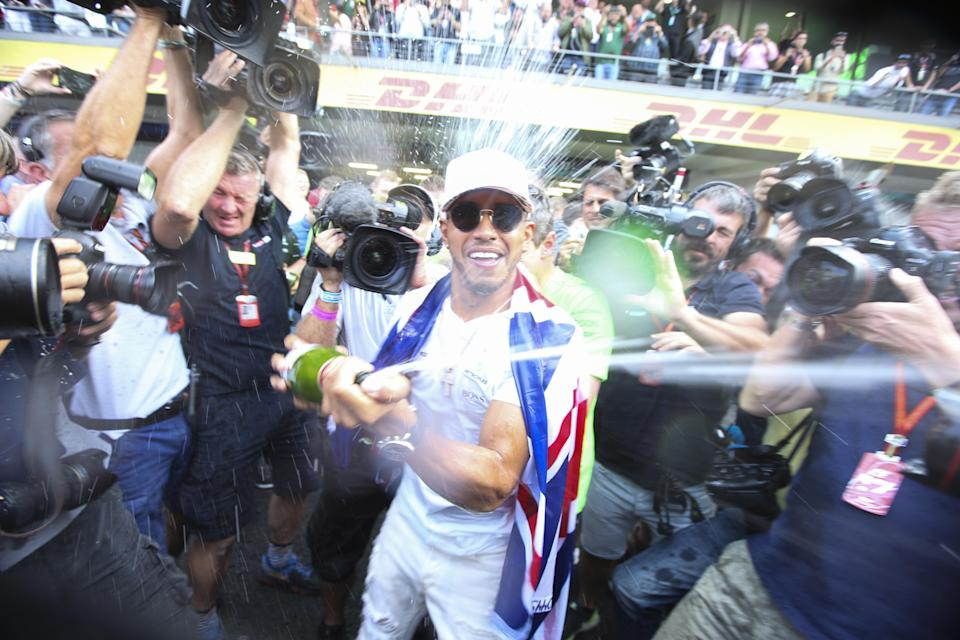 Flash and splash: Lewis Hamilton soaks photographers as he celebrates winning the 2017 Drivers' Championship at the Mexican Grand Prix