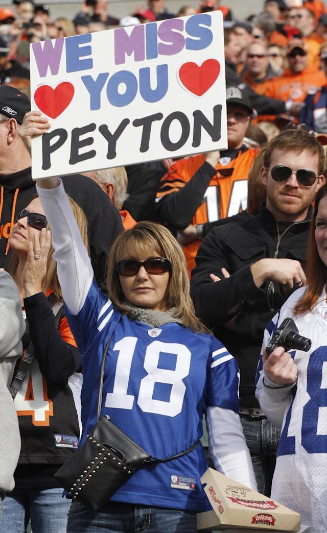 FILE - In this Nov. 4, 2012, file photo, a fan wearing and Indianapolis Colts jersey holds up a sign for Denver Broncos quarterback Peyton Manning during the first half of an NFL football game in Cincinnati. Manning returns to Indianapolis on Sunday, to face his old team for the first time since signing with the Broncos. (AP Photo/Tom Uhlman, File)