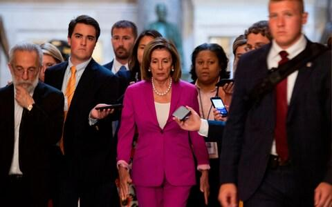 """US speaker of the House, Nancy Pelosi (C) walks with reporters, before the Democrat controlled House of Representatives passed a resolution condemning US President Donald Trump for his """"racist comments"""" - Credit: AFP"""
