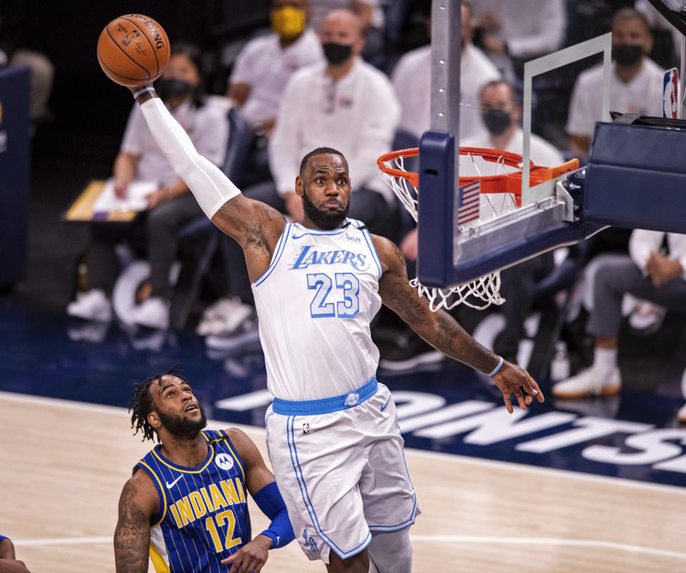 Los Angeles Lakers forward LeBron James (23) slam dunks the ball during the first half of an NBA basketball game against the Indiana Pacers in Indianapolis, Saturday, May 15, 2021. (AP Photo/Doug McSchooler)