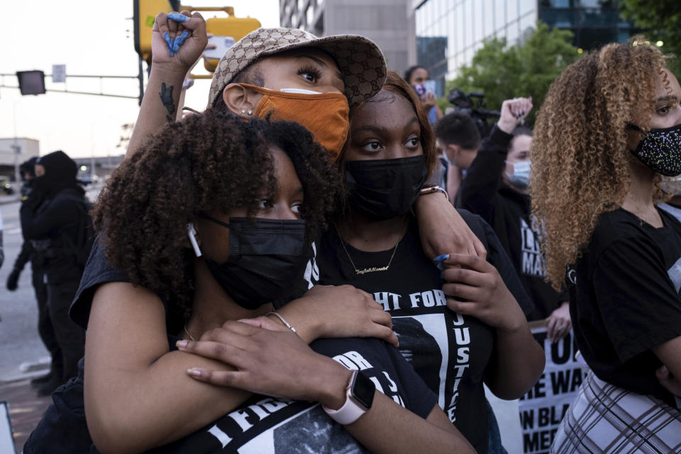 Chiara Campbell, from left, Nyasia Thompson and Jaylah Lesesne embrace following a march through downtown Atlanta after Derek Chauvin was found guilty of three counts in the death of George Floyd Tuesday, April 20, 2021. (AP Photo/Ben Gray)