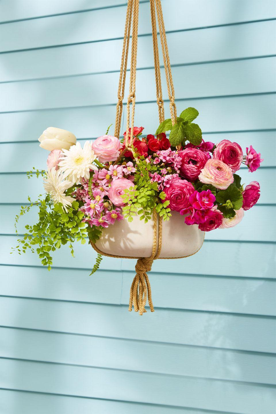 """<p>A pretty bouquet of flowers easily brightens any space. DIY your own hanging planter and attach it to your porch for a splash of color. <strong><strong><br></strong></strong></p><p><strong>RELATED: </strong><a href=""""https://www.goodhousekeeping.com/holidays/easter-ideas/g1906/easter-flowers/"""" rel=""""nofollow noopener"""" target=""""_blank"""" data-ylk=""""slk:Stunning Ways to Decorate With Flowers This Easter"""" class=""""link rapid-noclick-resp"""">Stunning Ways to Decorate With Flowers This Easter</a></p>"""