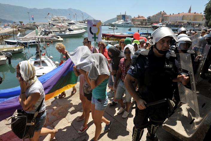 """Montenegro gay activists march during the first ever pride event in the Montenegrin seaside resort of Budva, Wednesday, July 24, 2013. Dozens of extremists shouting """"Kill the gays"""" have attacked gay activists as they were gathering for the first ever pride event in staunchly conservative Montenegro. The assailants threw rocks, bottles and various other objects at some 20 gay activists and supporters and at special police securing the event in the coastal town of Budva on Wednesday. (AP Photo/Risto Bozovic)"""