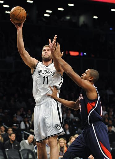 Brooklyn Nets' Brook Lopez (11) shoots over Atlanta Hawks' Al Horford (15) in the first half of an NBA basketball game, Sunday, March 17, 2013, at Barclays Center in New York. (AP Photo/Kathy Kmonicek)