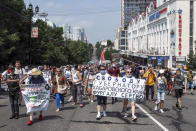 """People hold posters that read: """"Freedom for Khabarovsk region's governor Sergei Furgal"""" during an unsanctioned protest in support of Sergei Furgal, the governor of the Khabarovsk region, in Khabarovsk, 6100 kilometers (3800 miles) east of Moscow, Russia, Saturday, July 18, 2020. Tens of thousands of people in the Russian Far East city of Khabarovsk took to the streets on Saturday, protesting the arrest of the region's governor on charges of involvement in multiple murders. Local media estimated the rally in the city attracted from 15,000 to 50,000 people. (AP Photo/Igor Volkov)"""