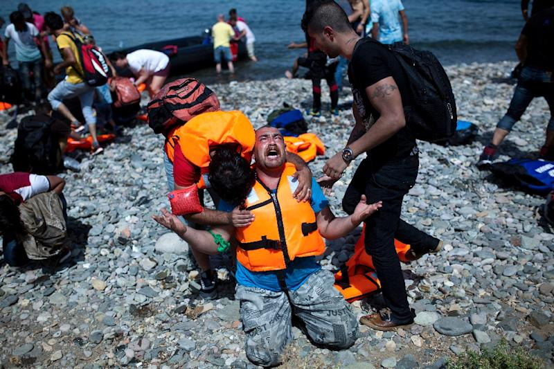 A refugee from Syria prays after arriving on the Greek island of Lesbos on an inflatable dinghy across the Aegean Sea from Turkey on September 7, 2015
