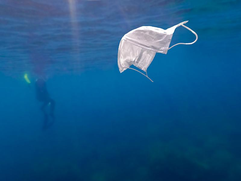Scuba divers are exploring underwater and cleaning up the ocean. Catch a disposable masks outbreak trash on the blue water. Trash in the beach threatening the health of oceans.