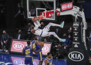 New York Knicks center Nerlens Noel hangs from the rim after a dunk against the Golden State Warriors during the first quarter of an NBA basketball game Tuesday, Feb. 23, 2021, in New York. (Wendell Cruz/Pool Photo via AP)